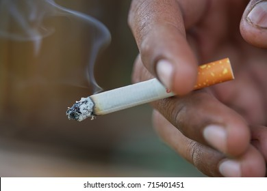 Close up man hand smoking cigarette.