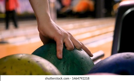 Close up for man hand taking a ball from a rack and throw it to the bowling lane. Media. The player throws a bowling ball that knocks down and rolls.