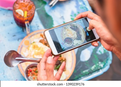 Close up of man hand taking food photo on table. Simple Thai menu street travel local food.