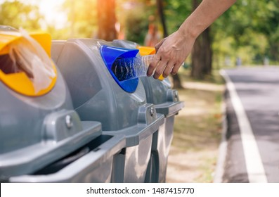 Close up of man hand throwing a plastic bottle into recycle dustbin. Garbage sorting before putting in garbage bin. Save the earth and Environmental concern concept