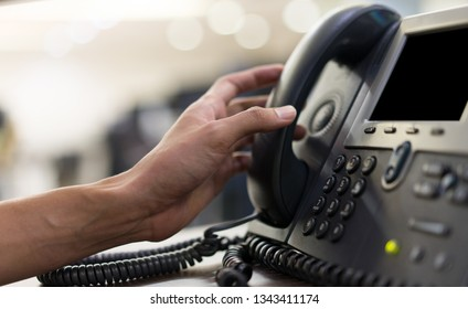 close up man hand touching telephone for call  or connecting with partner,vendor or customer at computer desktop operation room, hotline and helpline concept.