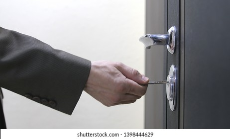 Close up of a man hand unlocks a house's door with key