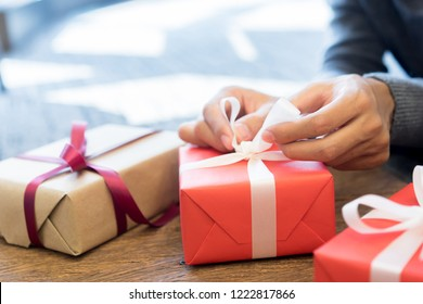 close up man hand unwrapping on white tied bow on red box for opening gift at living room house in merry christmas and happy new year festival celebrate concept