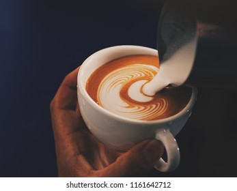 Close up man hands with coffee latte art.