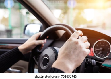 Close up of man hands driving a car during sunlight. Vintage filter