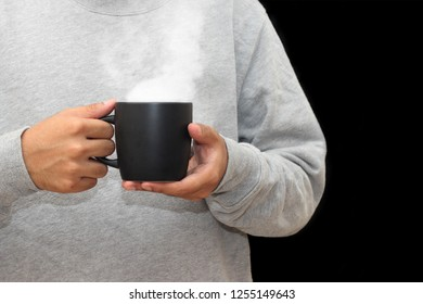 Close up of man hands holding black mug with blank copy space scree for your advertising text message or promotional content, sweet coffee or tea.