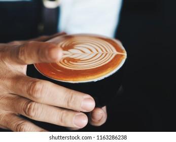 Close up man hands holding coffee latte art.