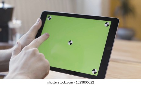 Close up of man hands holding digital tablet computer with green screen, scrolling, sliding and tapping his device. Stock footage. Sitting at the desk and using Ipad with chroma key.