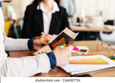 Close up of man hands holding documents while he is sitting in a business meeting .Table full of histogram and gadgets.