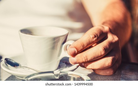 Close up of a man hands holding a hot coffe cups. Coffe time. Hand of man hold coffee or coffe cup at cafe in the morning. Cup of coffee. Coffee drink.
