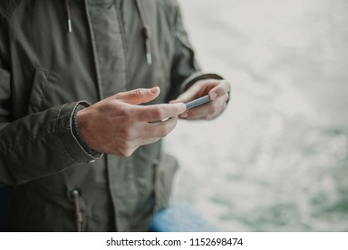 Close up of man hands holding a mobile phone while travel in a boat.