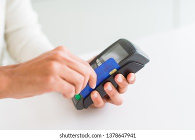 Close up of man hands holding point of sale terminal, dataphone for shopping paying using credit card