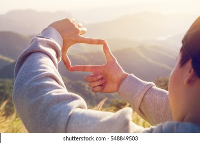 Close up of man hands making frame gesture with sunrise on moutain, Male capturing the sunrise, Future planning, sunlight outdoor.