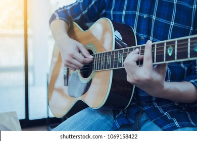 close up of a man hands playing guitar in home