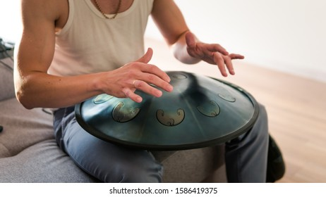 Close up of man hands playing hang drum indoors. Unusual music instrument. Concept of sound for meditation