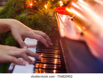 close up of man hands plays  on  Piano Keys with Christmas tree and decoration light, in the night of Christmas season, Christmas backgroumd with copy space