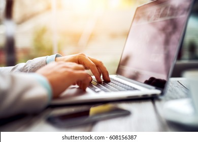 Close up of man hands typing text on laptop keyboard sitting at wooden table