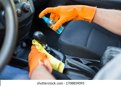 Close up of man hands using microfiber cloth and spray bottle while cleaning car interior gear stick.