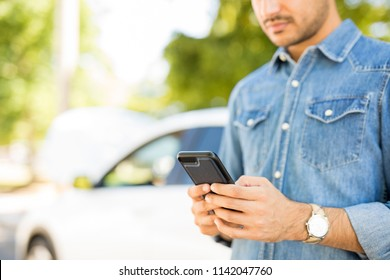 Close up of man hands using phone with broken car in background. Man calling roadside assistance for his breakdown car