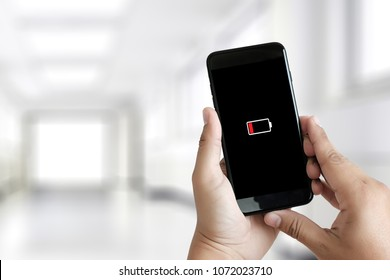 Close up man hands using smart phone battery low charged battery screen