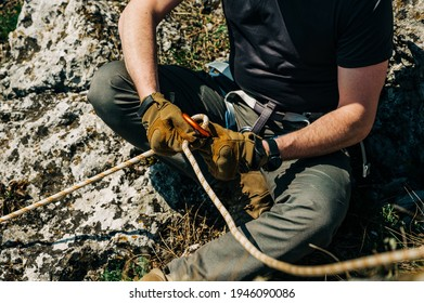Close up of a man in harness with rock climbing equipment getting ready to rappelling outdoor. He is preparing rope in figure eight for rappelling. Climber with gear and equipment on the belt.