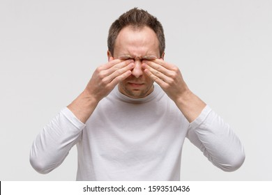 Close up of man has a problem with contact lenses, rubbing his swollen eyes due to pollen, dust allergy. Dry eye syndrome, watery, itching. Isolated on grey background, front view.