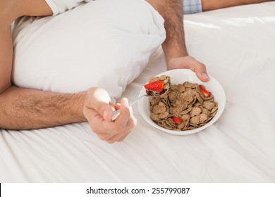 Close up of man having breakfast in bed at home in bedroom