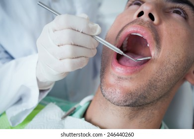 Close up of man having his teeth examined by dentist
