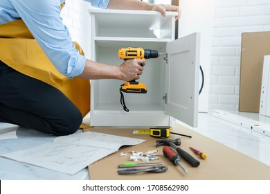 close up man holding cordless screwdriver machine and screws lie for screwing a screw assembling furniture at home