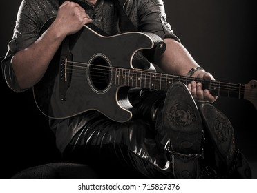 Close up of a man holding a guitar.