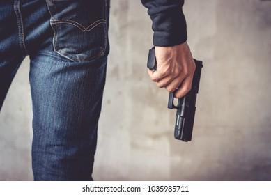 Close up of man holding hand gun. Man wearing blue jeans.