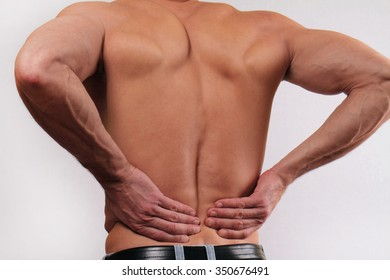 Close up of man holding his lower back. Man rubbing his painful back. . Pain relief concept