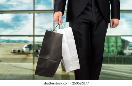close up of man holding shopping bags walking into airport