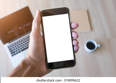 Close up of a man holding smartphone with blank screen mobile and laptop computer at coffee shop.