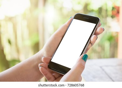 Close up of a man holding smartphone with blank screen mobile and laptop computer at coffee shop. Graphic display montage.