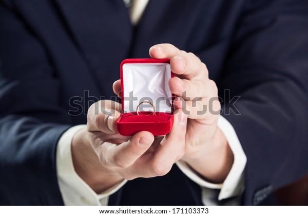 Close up do homem segurando anel de casamento e caixa de presente.