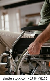 Close up of man holding wheel of wheelchair. Young disabled man in a wheelchair.