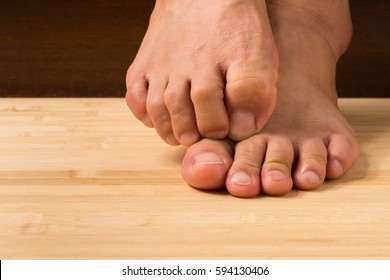 Close up a man with itchy feet uses his big toe to scratch his other foot on wooden floor.
