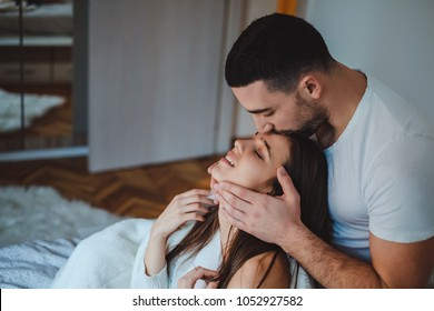 Close up of a man kissing girlfriends forehead in the bedroom while she is smiling
