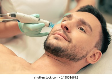 Close up of the man looking calm and hand in rubber glove holding a modern tool near his face during the skin nourishing procedure
