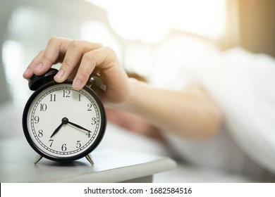 Close up of man lying in bed turning off hand reaching out for alarm clock color black Wake up late at morning at 7.20 am.