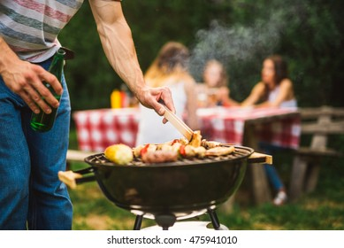 Close up of a man making barbecue and holding beer bottle.