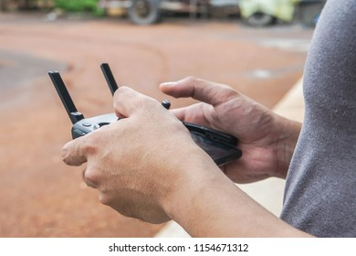 close up man play Drone by remote control joystick with smartphone