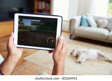 Close Up Of Man Playing Game On Digital Tablet At Home