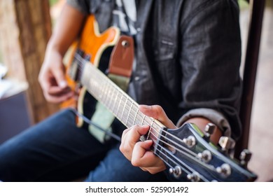Close up of a man playing guitar outdoors
