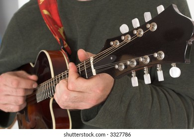 close up of man playing guitar over white background
