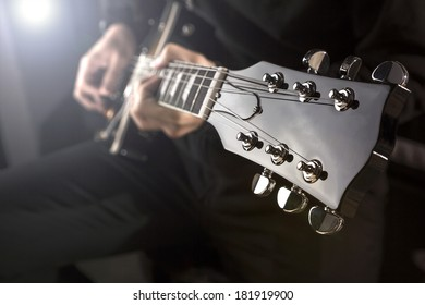 Close up of a man playing a guitar with spot light behind.