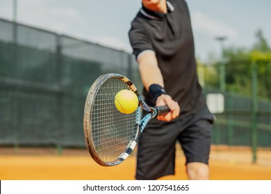 Close up of man playing tennis at court and beating the ball with a racket.