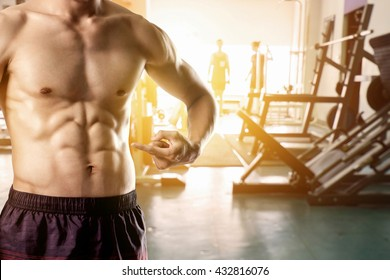 Close up of man pointing finger on his six pack at fitness gym sunrise with copy space. Exercise concept.