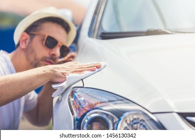 Close up of man polishing his car with microfiber cloth.